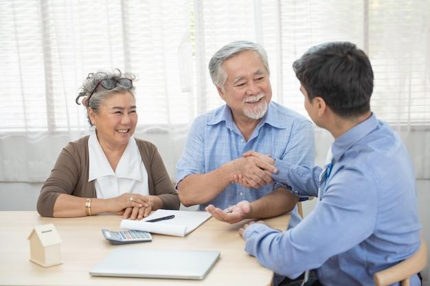 Le coppie senior soddisfatte sorridenti che fanno l'affare di acquisto di vendita che conclude la mano del contratto ottengono la chiave della casa dall'agente immobiliare, la famiglia più anziana felice e il mediatore si stringono la mano accettando di comprare la nuova casa alla riunione.