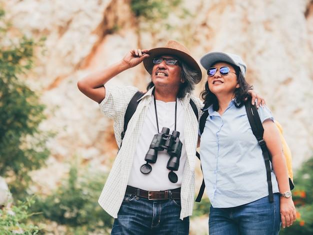 Le coppie senior viaggiano su vacanze estive. si tengono per mano e camminano insieme.