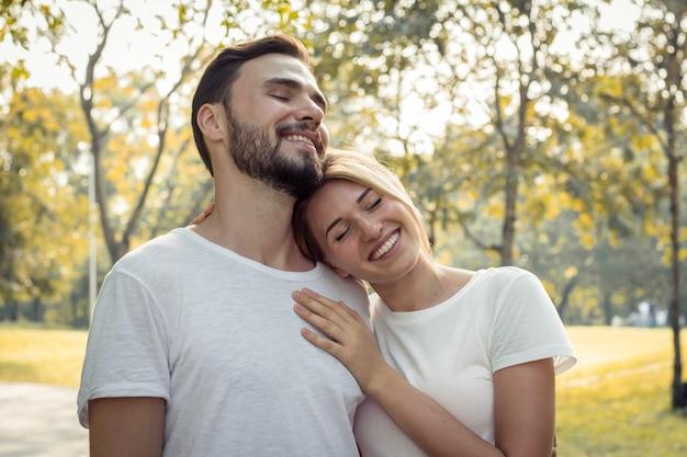Le coppie si mostrano amore nel parco.