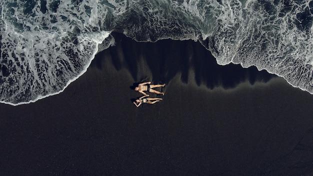 Le coppie si trovano su una sabbia nera vicino all'oceano