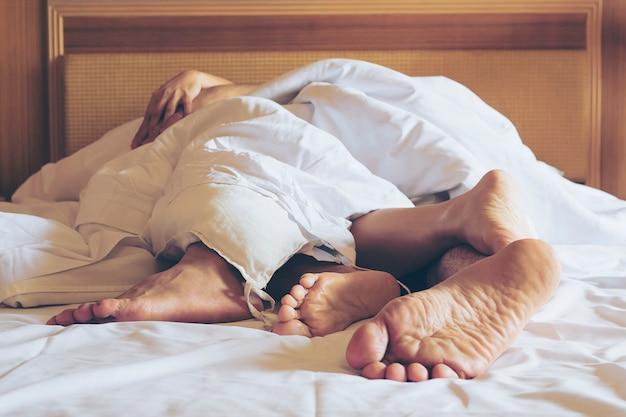 Le coppie sul letto bianco nel fuoco della camera di albergo ai piedi