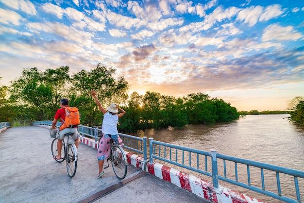Le coppie turistiche che guidano vanno in bicicletta nella regione del delta del mekong, ben tre, vietnam del sud. donna e uomo che si diverte in bicicletta tra verde bosco tropicale e canali d'acqua. cielo drammatico di tramonto di retrovisione.