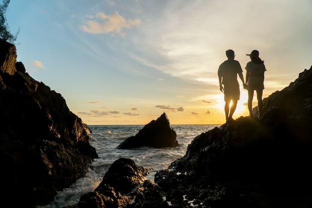 Le coppie viaggiano sul tramonto della spiaggia
