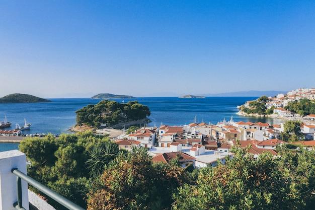 Le costruzioni bianche e marroni si avvicinano al mare circondato dagli alberi e dalle piccole isole a skiathos, grecia