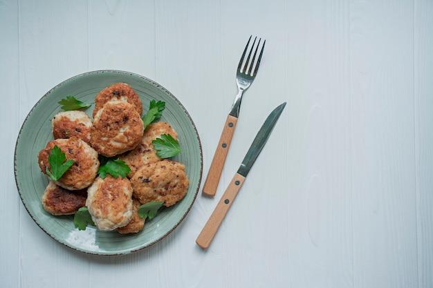 Le cotolette con le erbe sono servito su un piatto su un fondo di legno bianco.