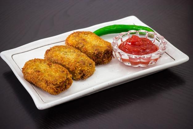 Le cotolette croccanti fritte dorate piccanti hanno servito la salsa di pomodori o il ketchup sul piatto bianco, preparano per l'iftar il ramadan. messa a fuoco selettiva