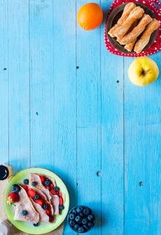 Le crepes casalinghe fresche sono servito su un piatto con le fragole ed i mirtilli, su un fondo di legno blu-chiaro,.