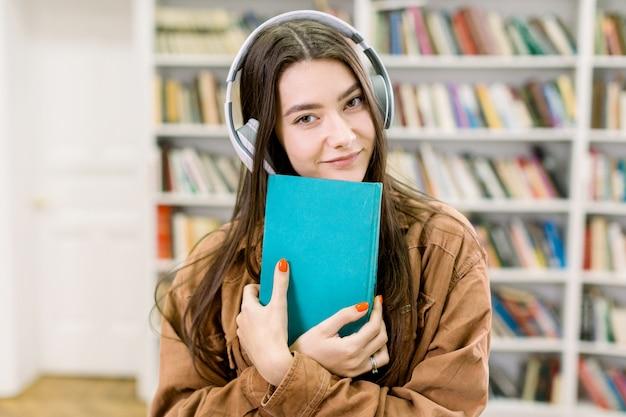 Le cuffie d'uso sorridenti della ragazza castana esaminano la macchina fotografica, posando con il libro blu in biblioteca, stando sullo spazio degli scaffali di libro con differenti libri