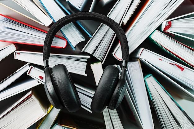 Le cuffie nere aeree wireless si trovano sui libri. il concetto di apprendimento attraverso un audiolibro. per ascoltare il libro.