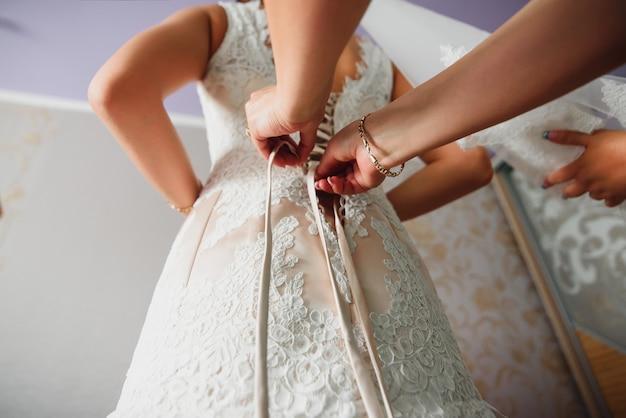 Le damigelle aiutano a raccogliere la damigella e allacciare il vestito