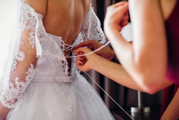Le damigelle allacciano l'abito bianco da sposa sulla schiena della sposa il giorno del matrimonio