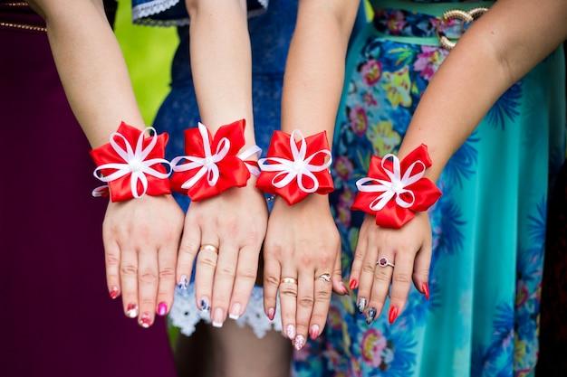 Le damigelle mostrano bracciali di fiori sulle mani