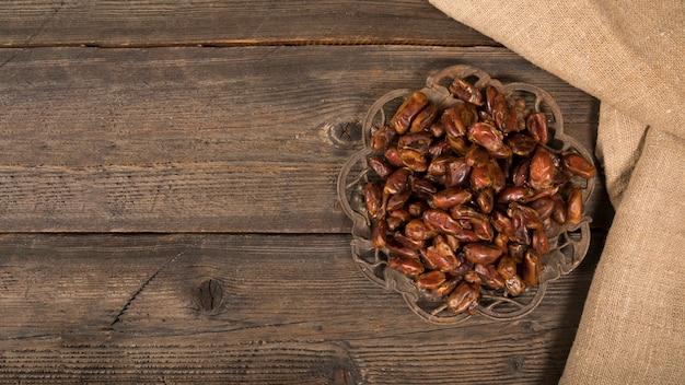 Le date fruttificano sul piatto sulla tavola di legno