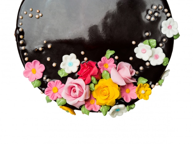 Le decorazioni del dolce di cioccolato del primo piano di vista superiore con frutta variopinta della glassa su fondo bianco