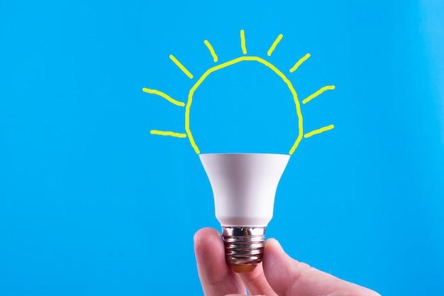 Le dita tengono un frammento di una lampada elettrica sul blu