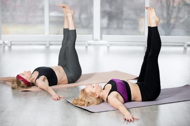 Le donne anziane che fanno doppio esercizio di sollevamento della gamba dritta
