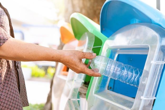 Le donne anziane gettano via la spazzatura nel cestino / spazzatura, classificando i rifiuti / immondizia prima di gettarli nel cestino