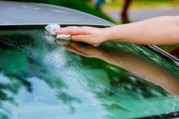 Le donne asciugano a mano asciugandosi la superficie dell'auto con un panno in microfibra dopo il lavaggio.