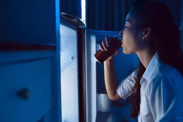 Le donne asiatiche aprono il frigorifero, bevono bevande analcoliche di notte