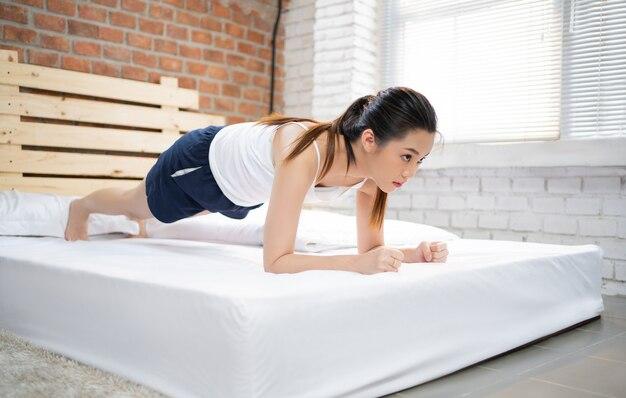 Le donne asiatiche che si esercitano a letto la mattina, si sente rinfrescata