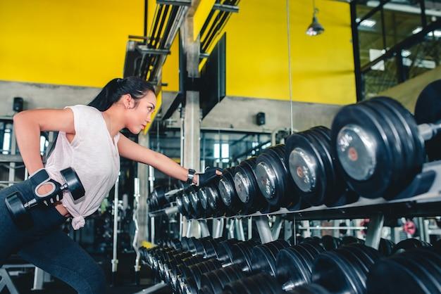 Le donne asiatiche che si esercitano con i manubri nella dumbbell bench press sono una posizione popolare per le giovani donne in forma.