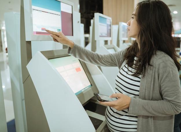 Le donne asiatiche confermano il peso degli articoli trasportati utilizzando il computer