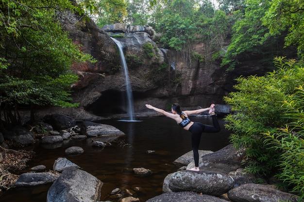 Le donne asiatiche della ragazza sta giocando lo yoga davanti alla cascata