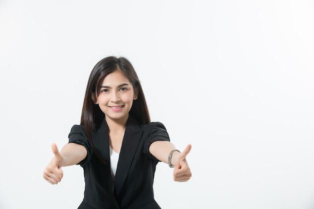 Le donne asiatiche di affari stanno sorridendo e lanciano sul segno della mano per lavorare felice e successo e vincere
