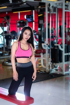 Le donne asiatiche di forma fisica stanno nel club di salute dell'interno e di forma fisica della palestra di sport con l'attrezzatura di esercizio di sport fondo della palestra.