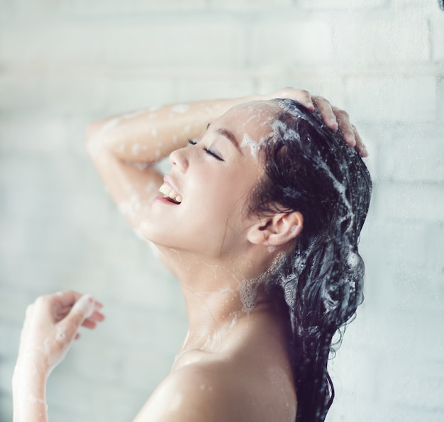 Le donne asiatiche facevano il bagno e lei stava facendo il bagno e lavando i capelli. è felice