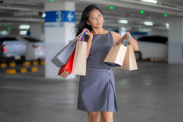 Le donne asiatiche fanno shopping felice nei grandi magazzini, nelle borse della spesa
