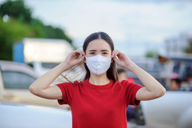 Le donne asiatiche i thailandesi usano la maschera facciale o la maschera chirurgica per proteggere il virus della corona, covid 19, nuova vita normale delle persone nel sud-est asiatico, le donne tailandesi usano la maschera in strada pedonale