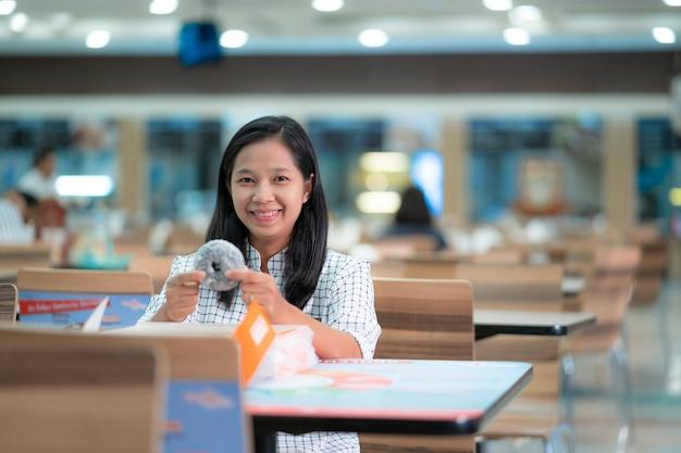 Le donne asiatiche mangiano felicemente le ciambelle al negozio