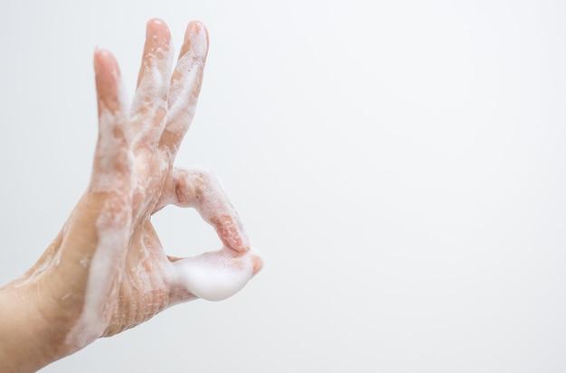Le donne asiatiche si lavano o puliscono le mani con il sapone e fanno una mano a forma di cuore, inviano incoraggiamento durante l'epidemia di covid-19.