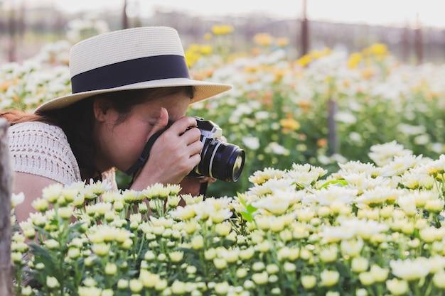 Le donne asiatiche stanno prendendo la foto un fiore bianco del crisantemo in un giardino floreale