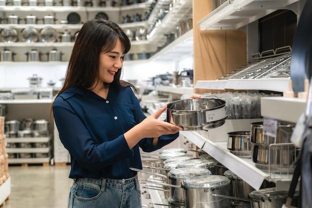 Le donne asiatiche stanno scegliendo di acquistare nuovi utensili da cucina nel centro commerciale. shopping per generi alimentari e casalinghi.