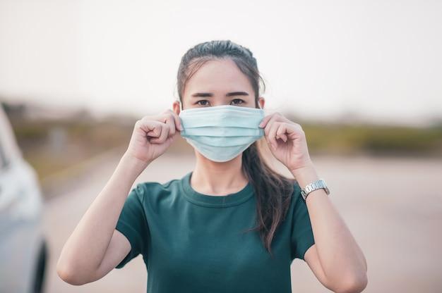 Le donne asiatiche usano la maschera chirurgica o la maschera facciale alla strada parcheggiata auto all'aperto