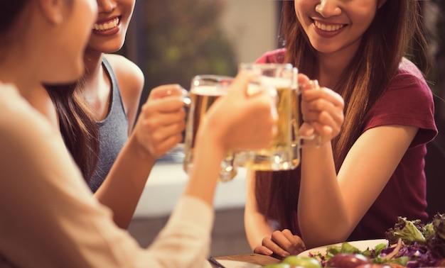 Le donne bevono birra e gli occhiali tintinnanti in un ristorante