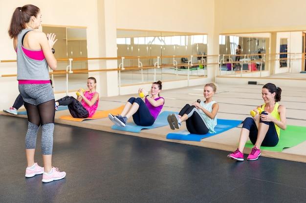 Le donne che fanno manubri si esercita in un allenamento di gruppo in una sala fitness