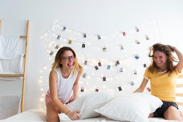 Le donne che giocano i cuscini combattono insieme sul letto