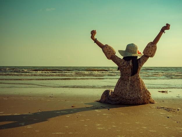 Le donne che indossano abiti vintage sono sedute sulla spiaggia con eccitazione per rilassarsi. le gite in spiaggia estive sono molto buone.