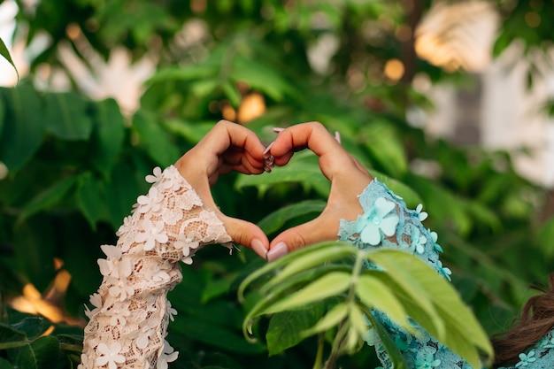 Le donne che mostrano il cuore con le mani