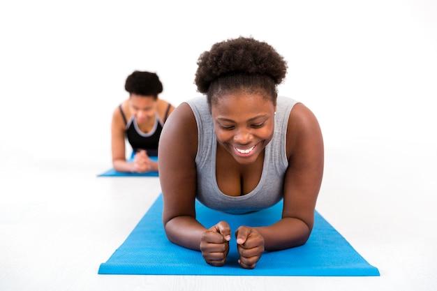 Le donne che praticano fitness sul tappetino