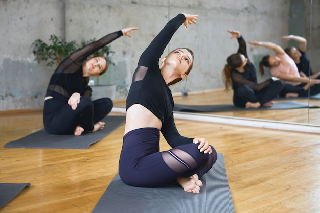 Le donne che praticano l'allungamento nella posa del loto su stuoie.