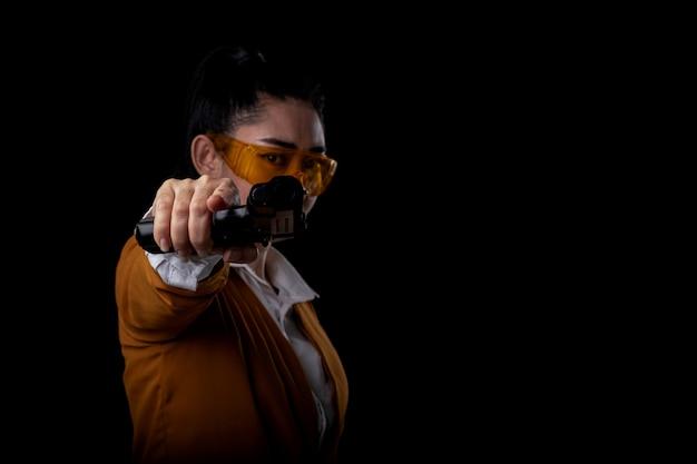 Le donne che puntano una pistola guardano la telecamera, ritratto bella donna asea che indossa un abito giallo con una mano che tiene la pistola sulla superficie nera, giovane ragazza sexy capelli lunghi con una pistola