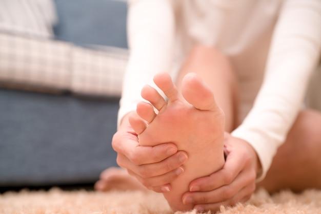 Le donne che soffrono di dolore alla caviglia del piede toccano il suo piede doloroso, il concetto di assistenza sanitaria e medicina