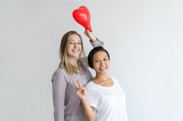 Le donne che tengono il cuore hanno modellato il pallone e stanno mostrando il segno di vittoria