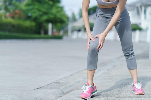 Le donne con dolore al ginocchio. sport che esercita lesioni. donna nel dolore mentre corre.