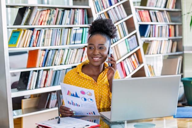 Le donne d'affari nell'abbigliamento casual lavorano allo scrittorio per l'analisi contabile e del piano aziendale