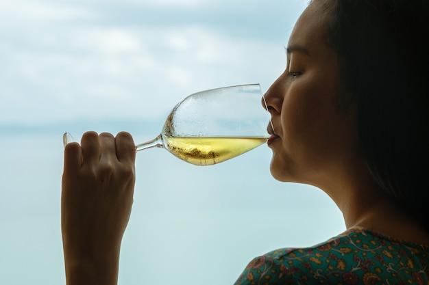 Le donne del primo piano bevono il vino bianco con un bicchiere di vino sul fondo di vista del mare nella sera